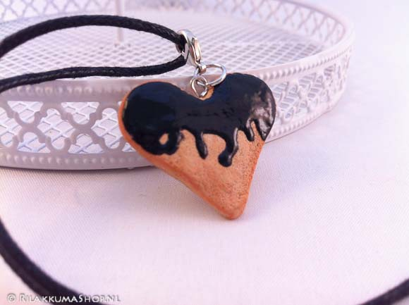 Kawaii cute heart cookie with black syrup on wax cord